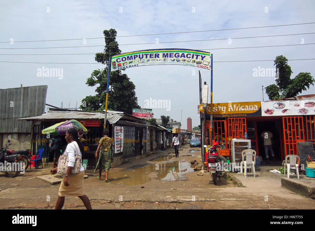 People walking in the street, in front of a commercial zone called Computer Megacity,  in the large city of Lagos, - Stock Image