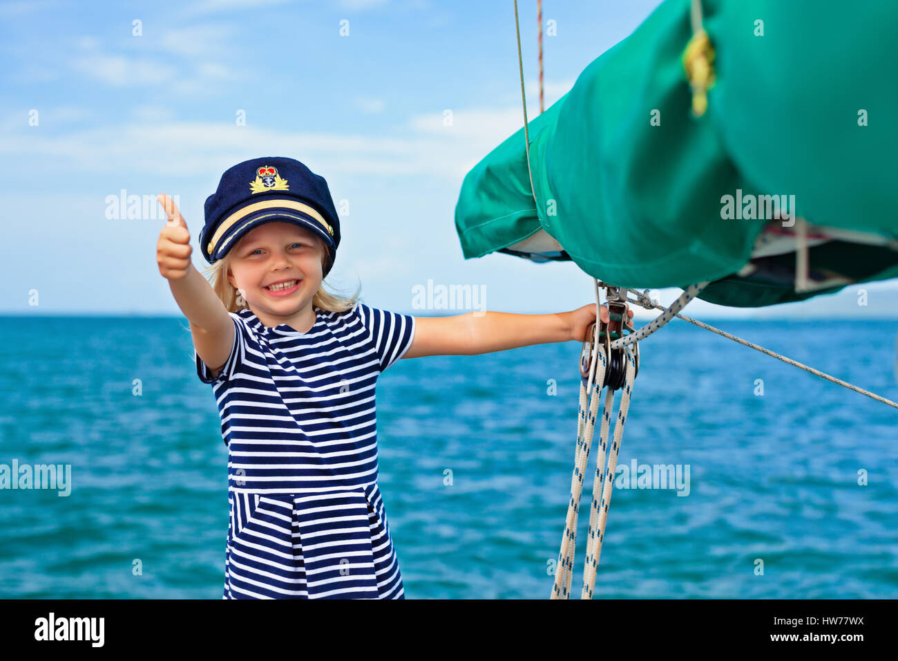 Happy little baby captain on board of sailing yacht watching offshore sea on summer cruise. Travel adventure, yachting - Stock Image