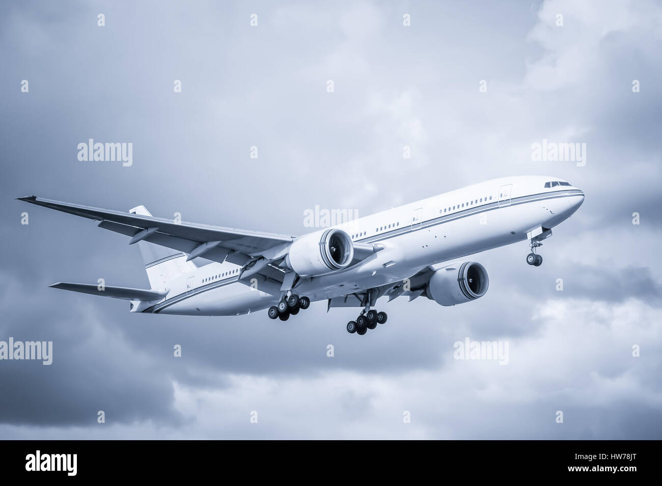 cool toned unmarked passenger aircraft landing - Stock Image