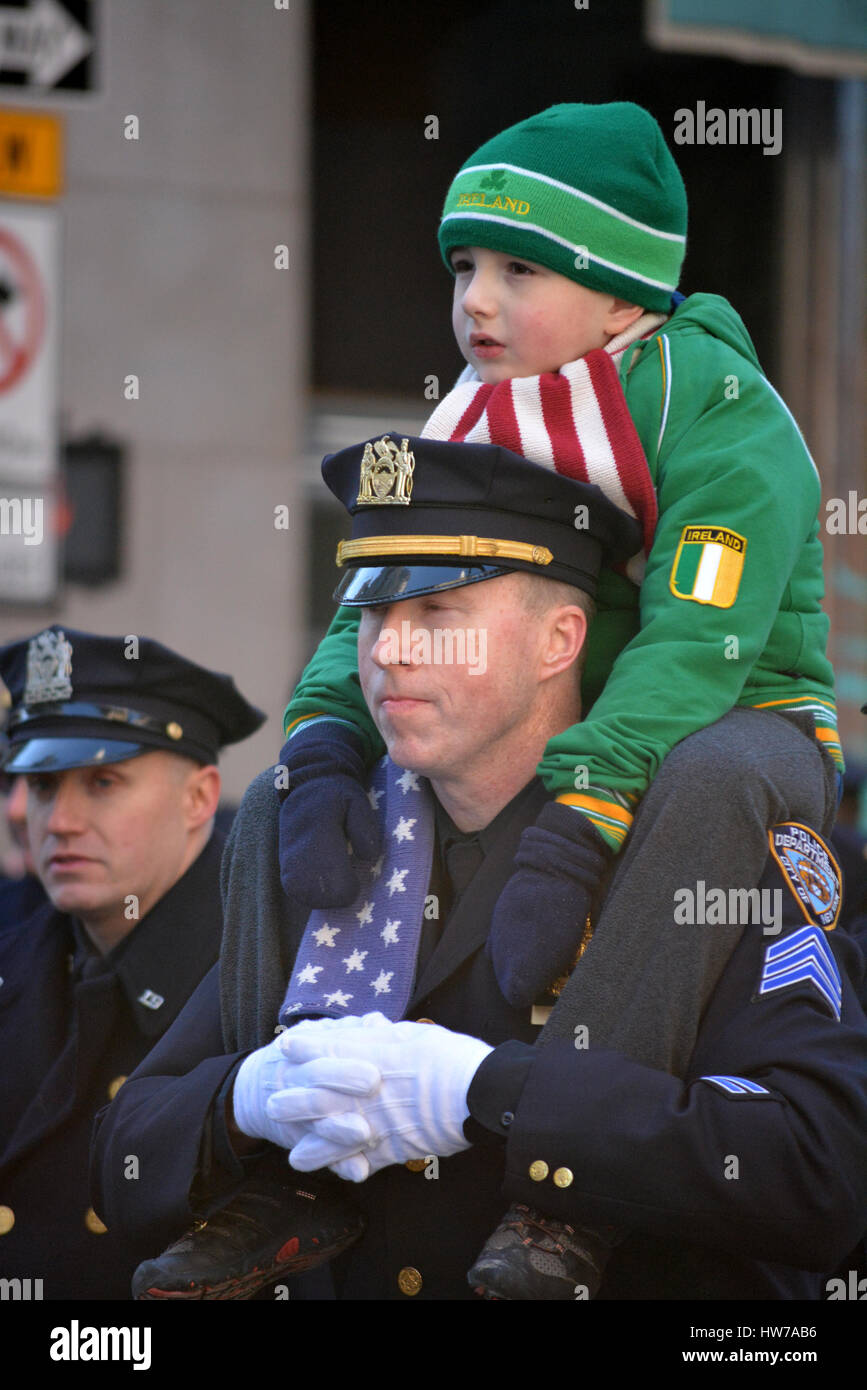 334b46f4 NYPD officer carrying a young boy on his shoulders during the New York City  St.