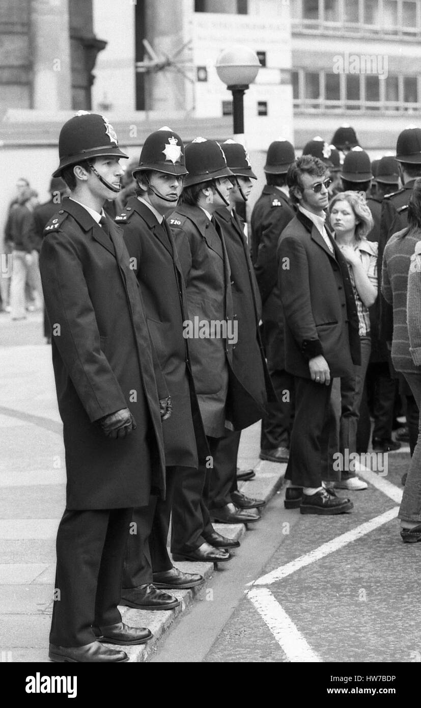 A music fan in Teddy Boy fashion stands with a line of police officers during the Rock and Roll Radio Campaign march - Stock Image