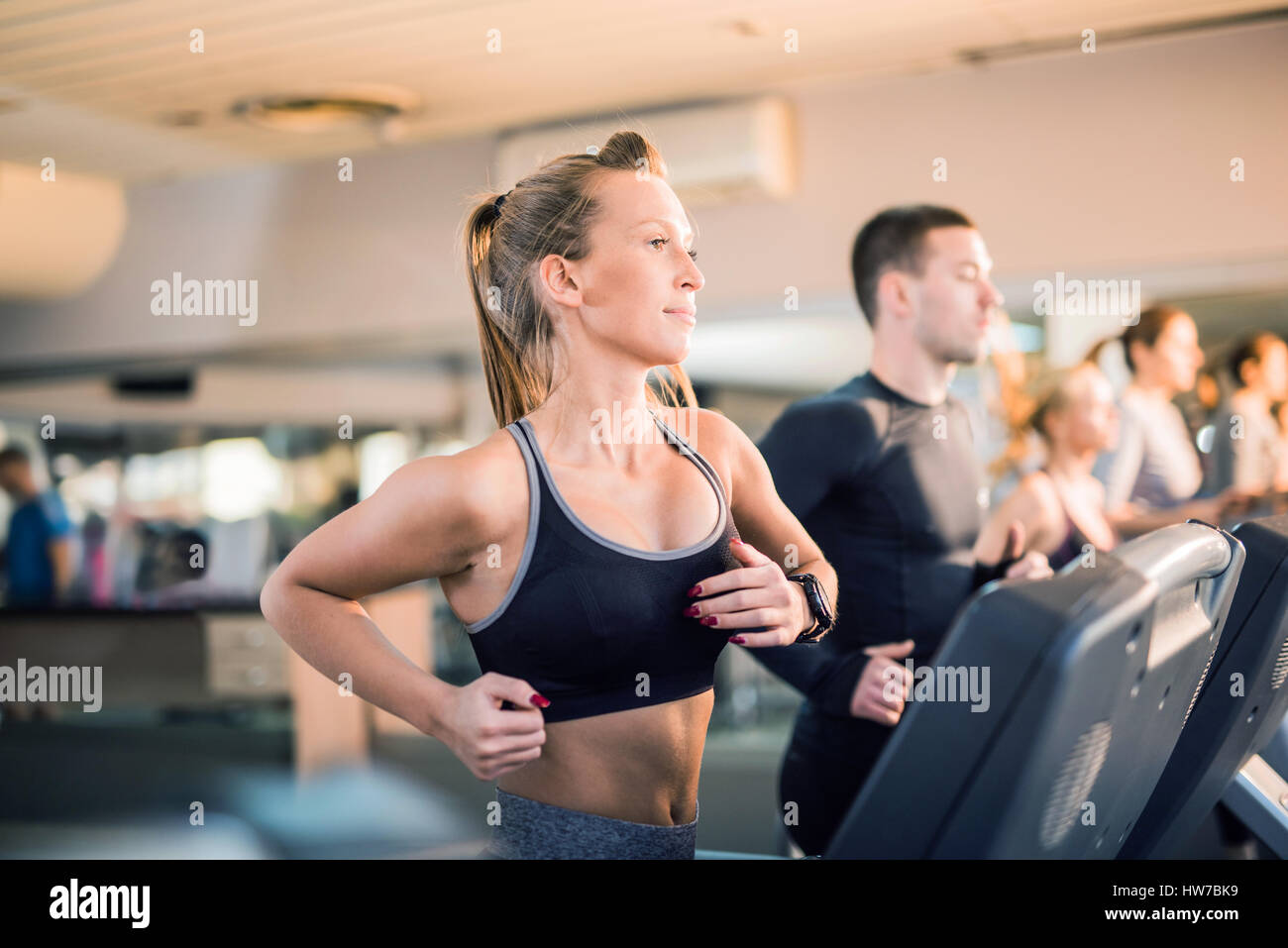 Beautiful young people running on a treadmill in health club - Stock Image