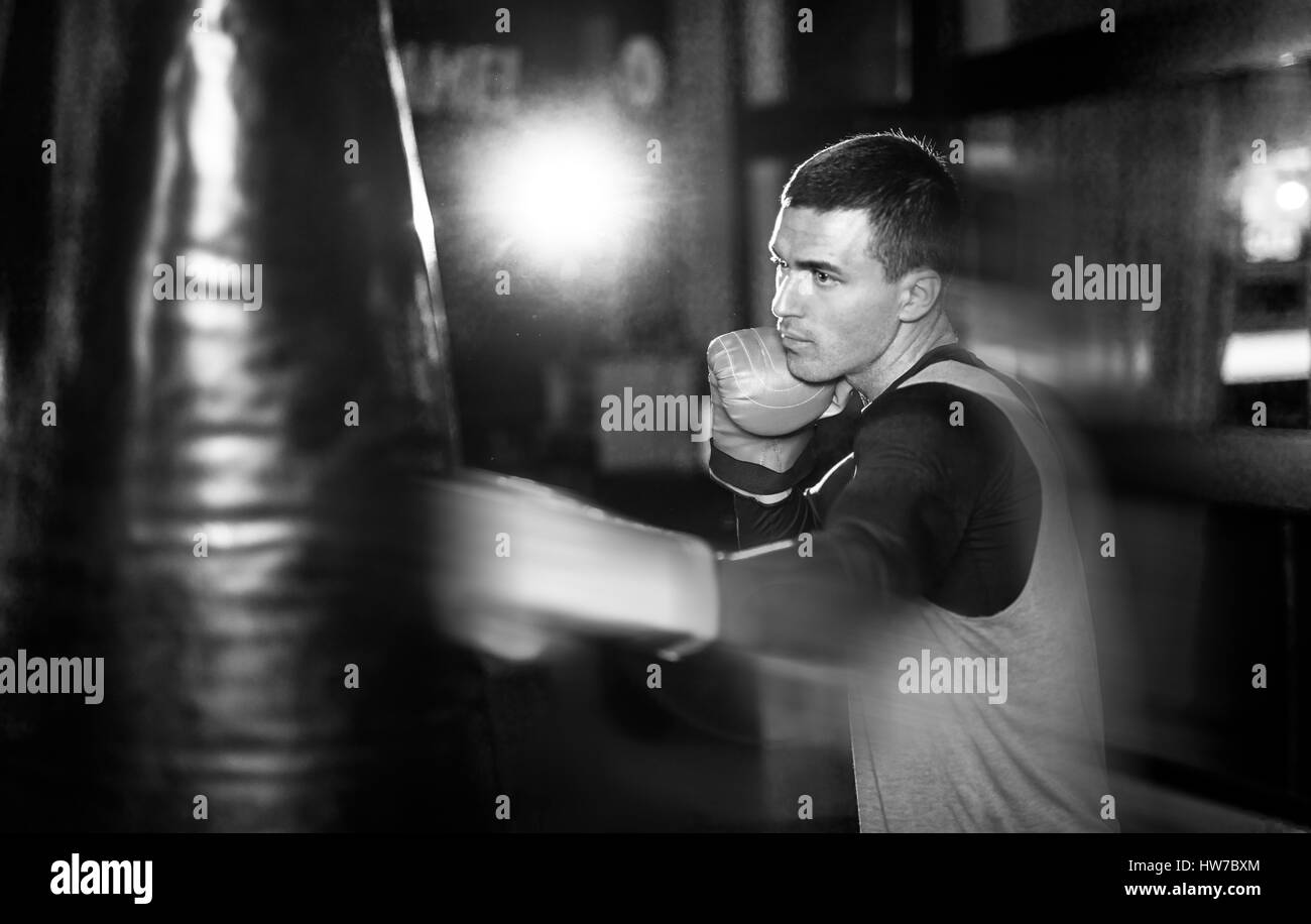 Young athlete boxer training with a punching bag Stock Photo