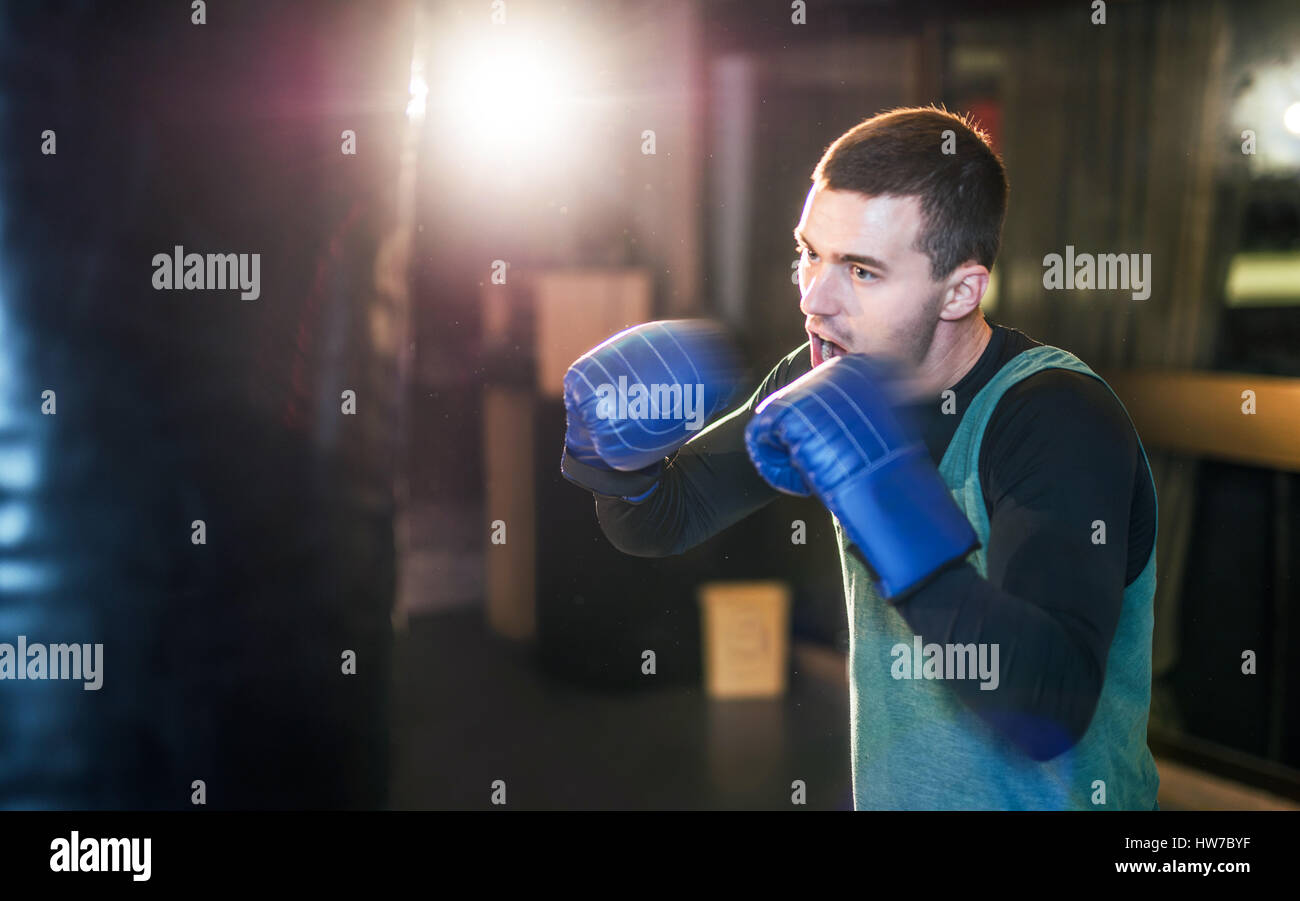 Young athlete boxer training with a punching bag - Stock Image