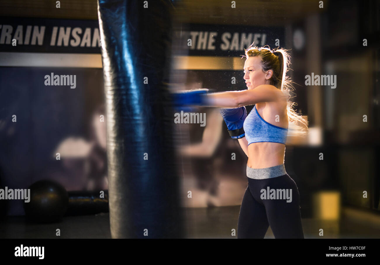 Young female athlete boxer training with a punching bag - Stock Image
