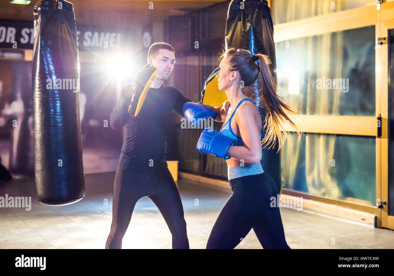 Coach teaching young woman how to box - Stock Image