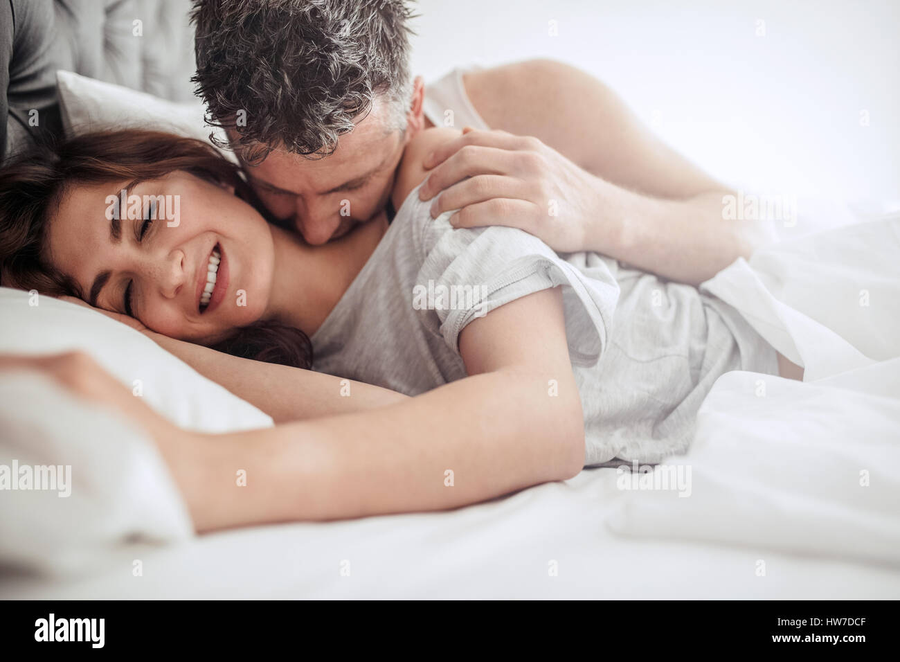 Wonderful Beautiful Passionate Couple Waking Up In Bed. Man Kissing On Neck Of Woman,  Both Lying On Bed