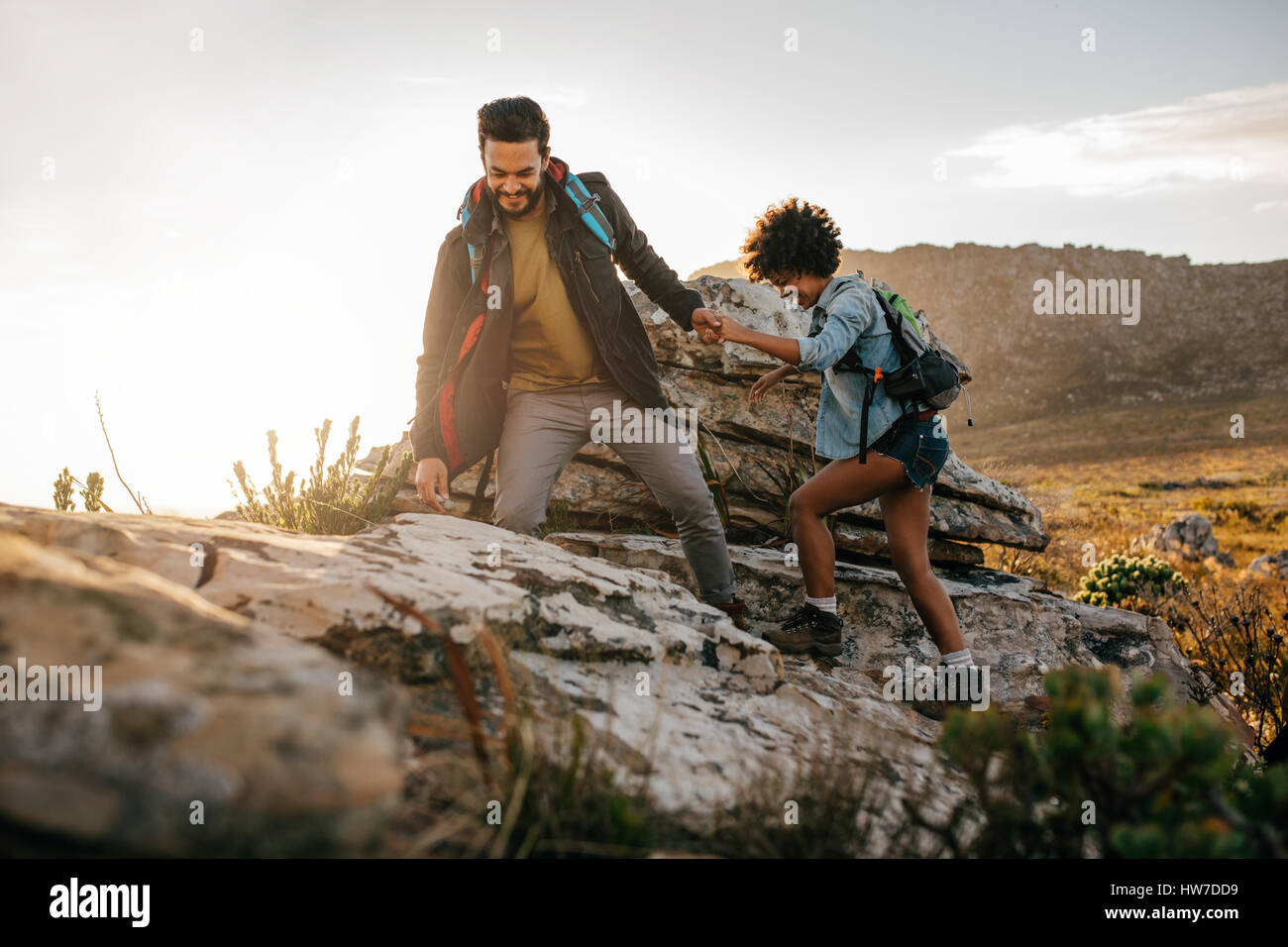 Young man helping friend to climb up the rock. Young couple hiking in nature. - Stock Image