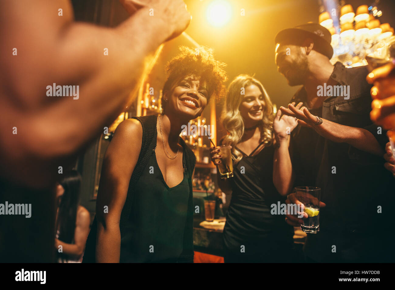 Image of happy young people having fun at disco. Group of friends enjoying a party at nightclub. - Stock Image