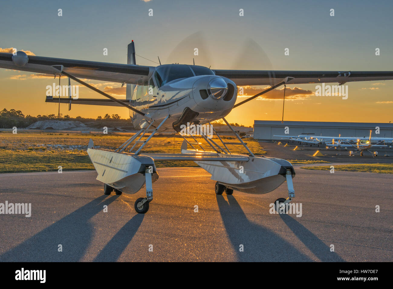 Float equipped Cessna 208 Caravan aircraft with engine running, backlit by the setting sun - Stock Image