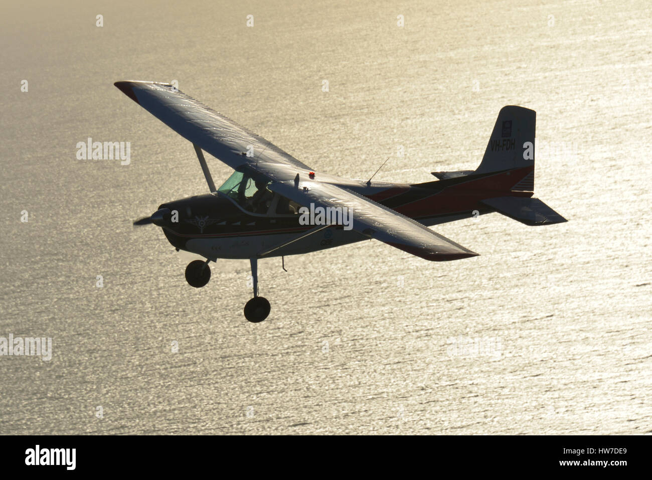 Cessna 180 Skywagon aircraft aircraft in silhouette, backlit by sun reflecting off the ocean. - Stock Image