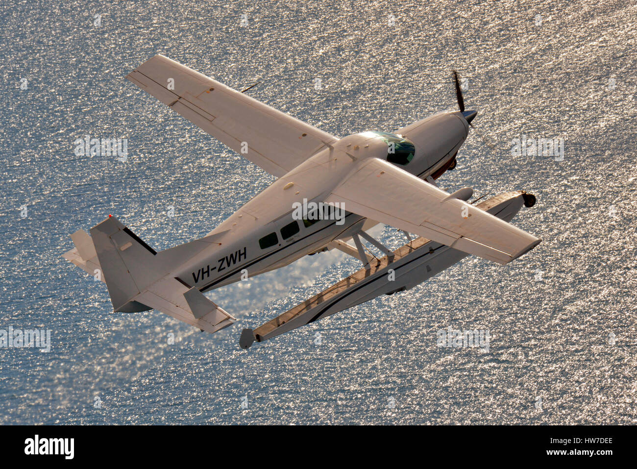 Float equipped Cessna 208 Caravan aircraft backlit by sun reflecting off the ocean. - Stock Image