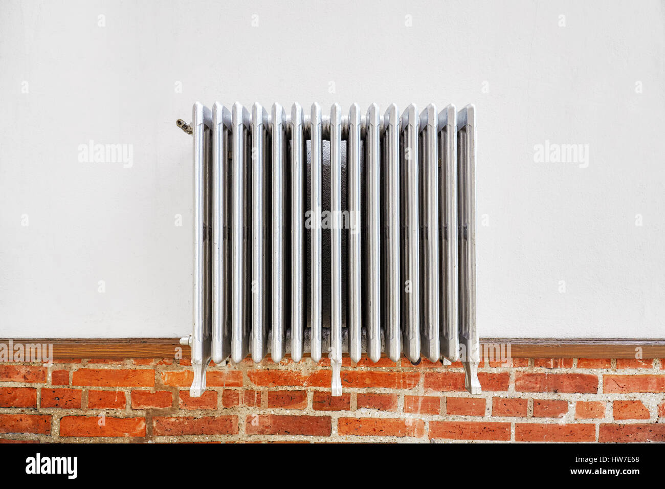 Old heating radiator on a wall. - Stock Image