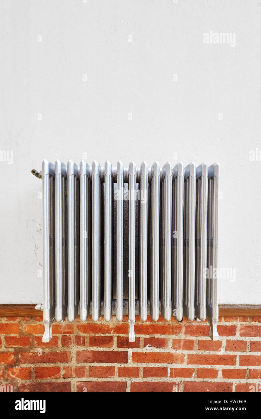 Old heating radiator on a wall, space for text. - Stock Image