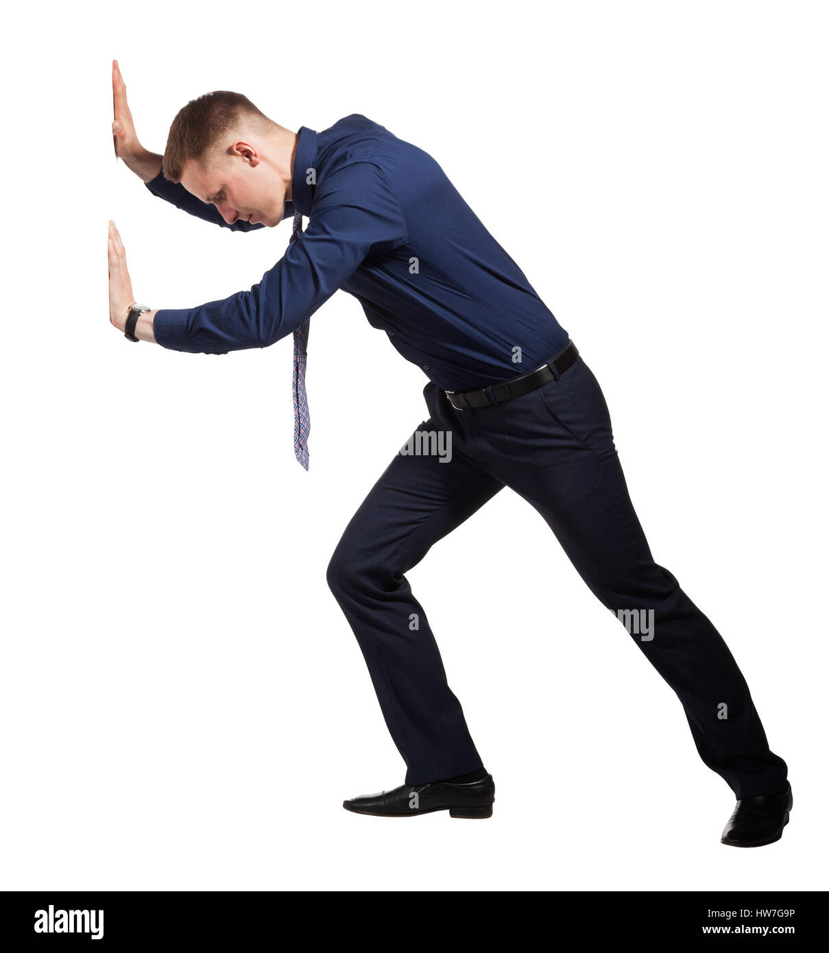 Young Businessman pushing wall, on white - Stock Image
