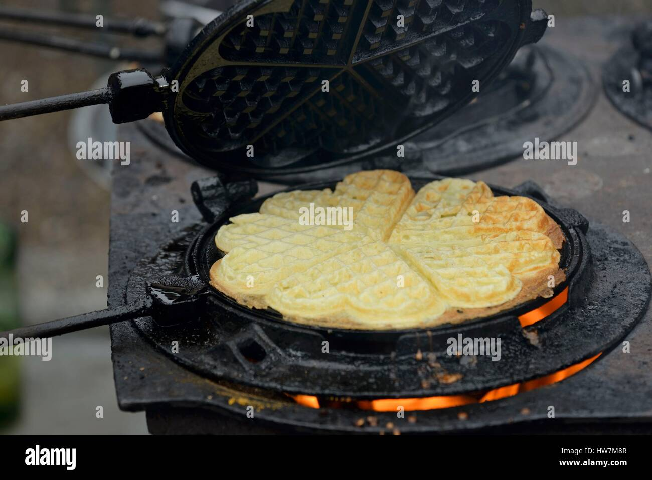 France, Vosges, Girmont Val d Ajol, Foire aux Andouilles, cooking waffles with old, stove 4 holes and mold - Stock Image