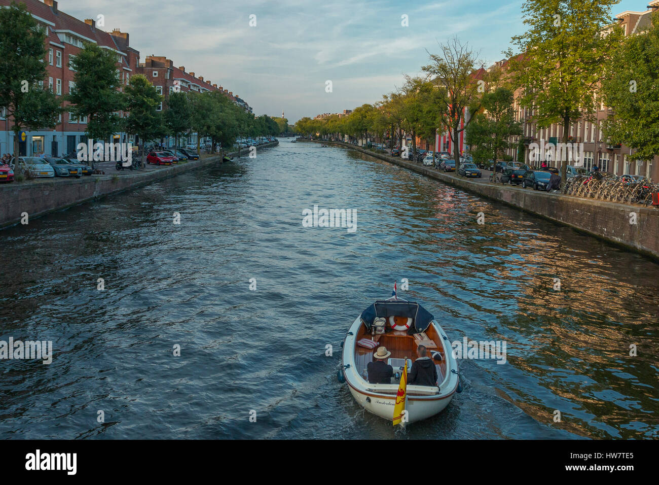 AMSTERDAM, NETHERLANDS- SEPTEMBER 24, 2016: Boaters on Kostverlorenvaart canal around sunset. - Stock Image