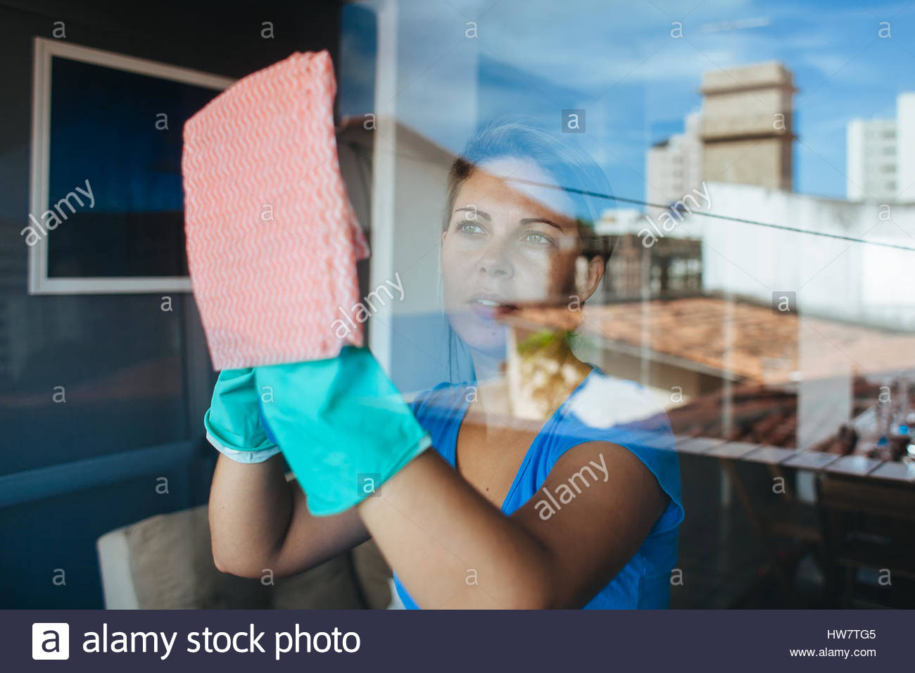 People, housework and housekeeping concept - happy woman in gloves cleaning window with rag and cleanser spray at - Stock Image