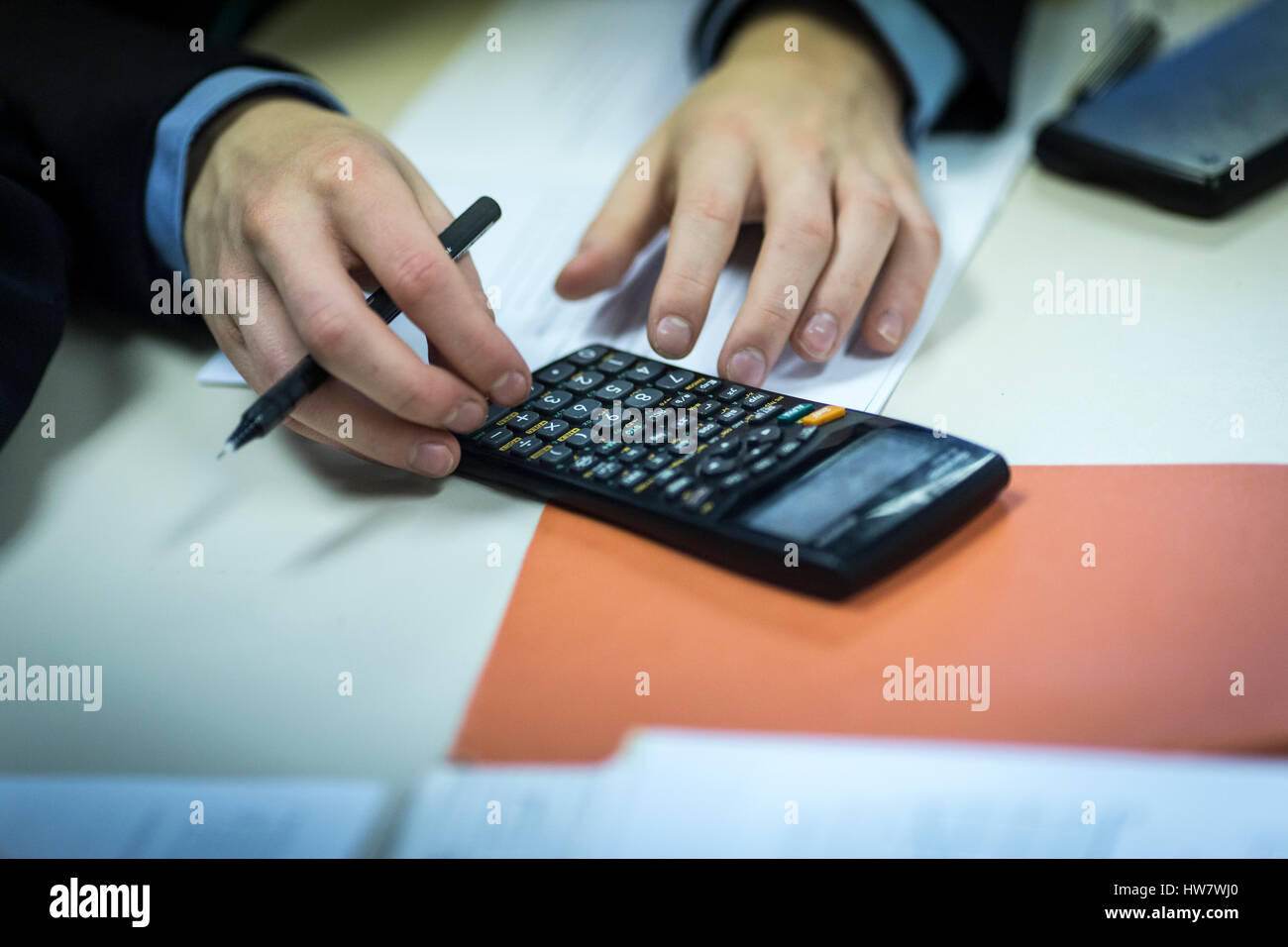 a male pupil uses a calculator during a lesson - Stock Image