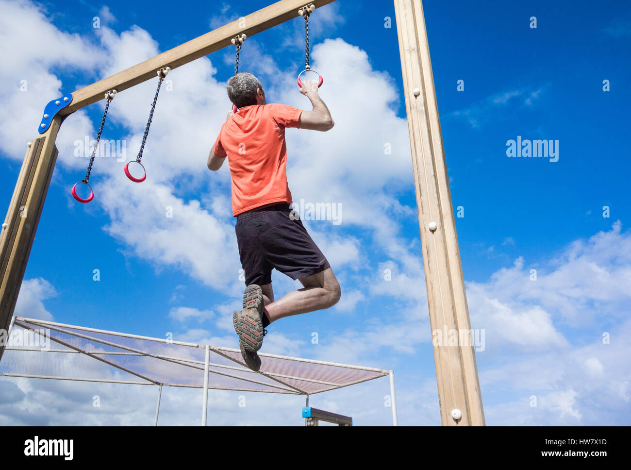 Mature man performing pull ups on rings in park - Stock Image