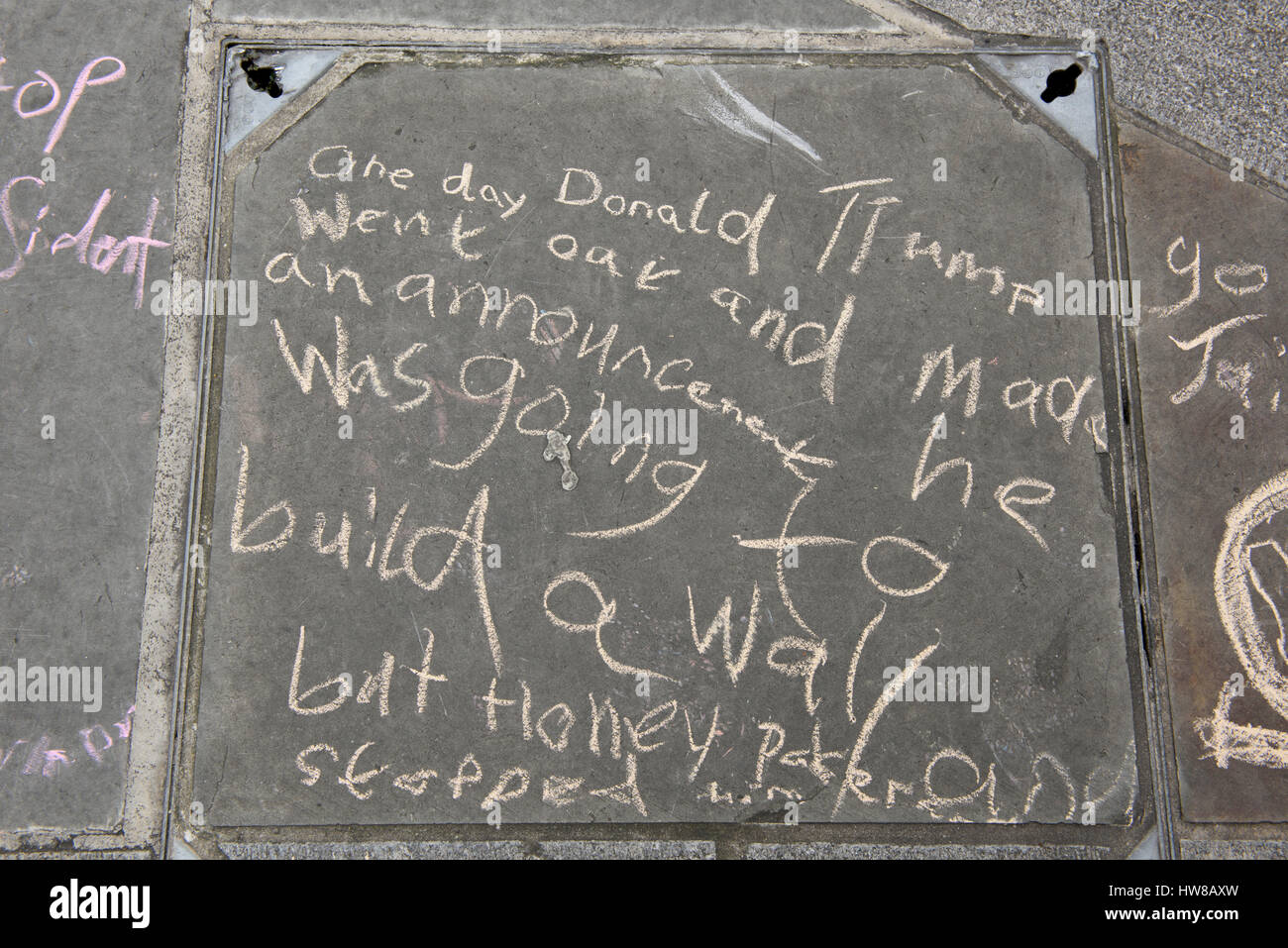 Anti-Trump and anti-racism message about the 'Donald Trump going to build a wall' is written on the pavement - Stock Image