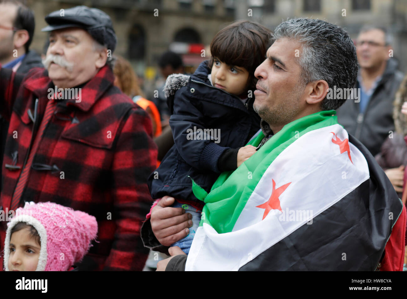 A Syrians father wears a Syria Independence flag over his shoulders and carries his daughter in his arms. Syrians Stock Photo