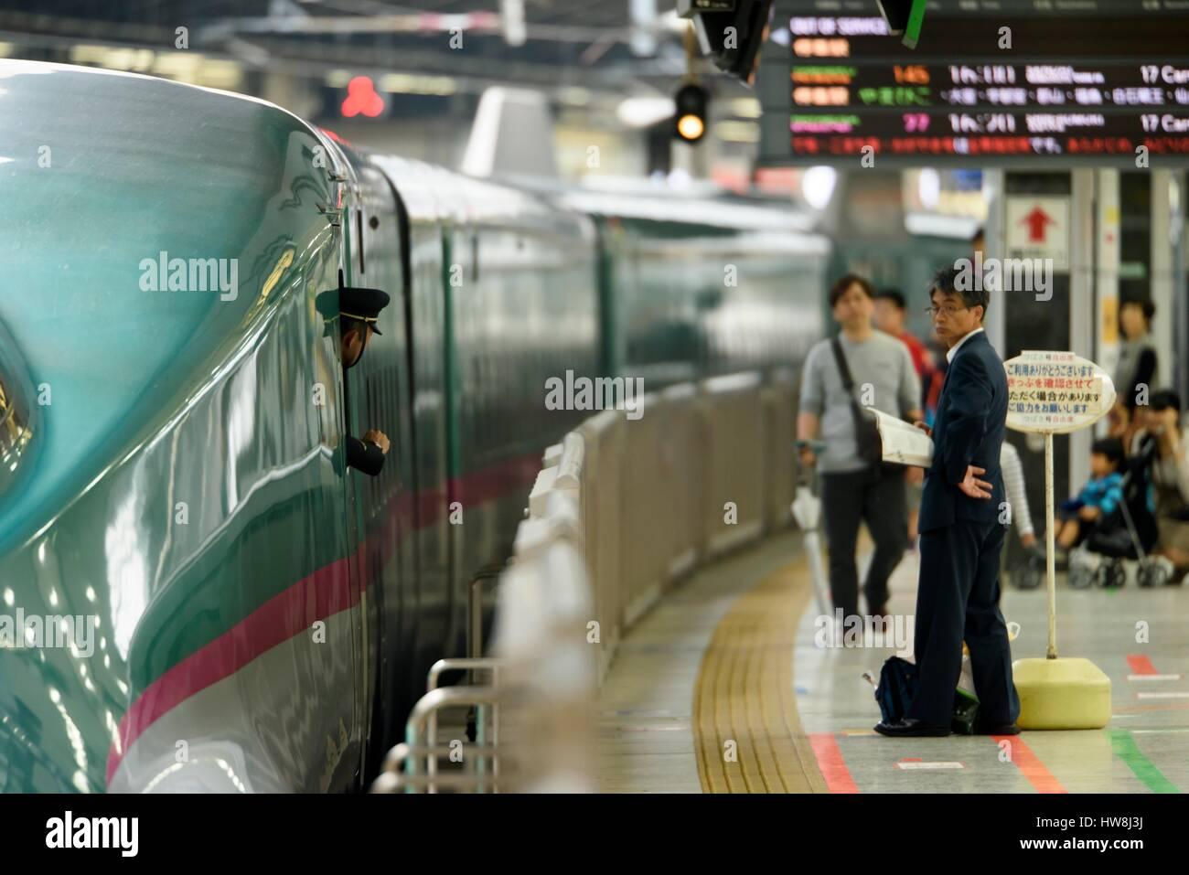 Japan, Honshu island, Tokyo, Central train station, A man to embark the Shinkansen as the train driver observes - Stock Image