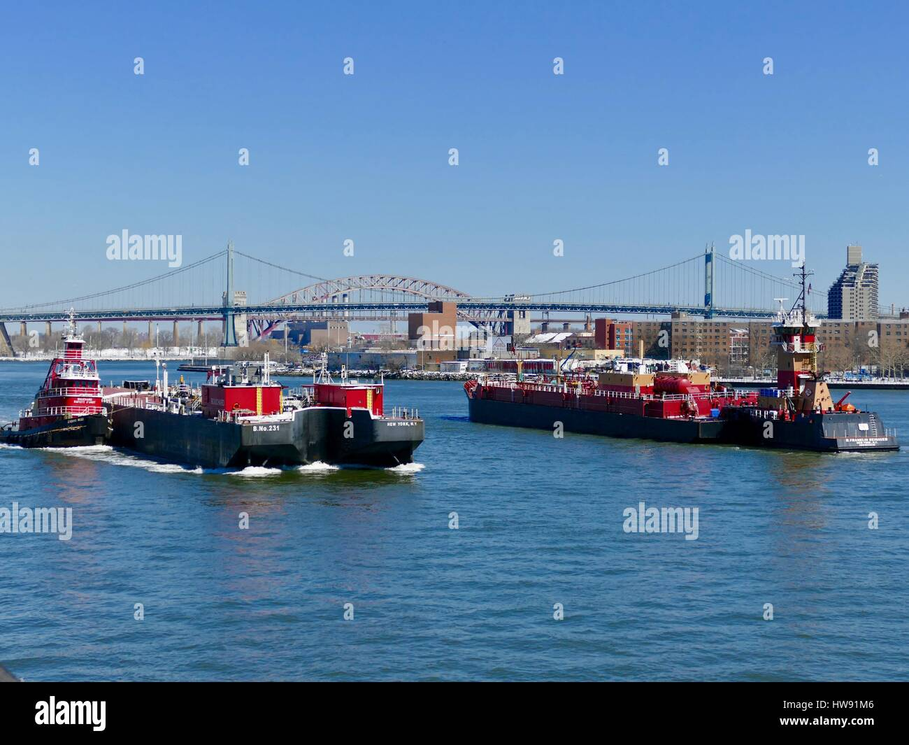 East River boat traffic; red barges and tugboats with RFK bridge in background. New York, New York, USA - Stock Image