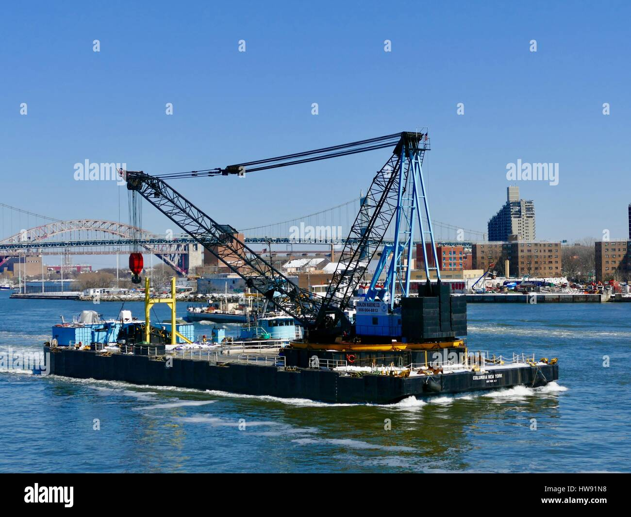 Commercial barge with crane, light blue trim, heading down the East River, New York, New York, USA - Stock Image