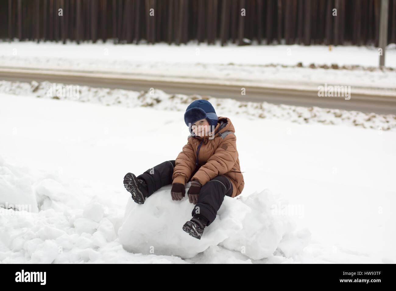 warmly dressed boy walking on a winter street - Stock Image