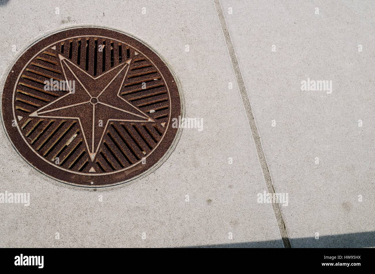 Attractive man hole cover decorated with a star. - Stock Image