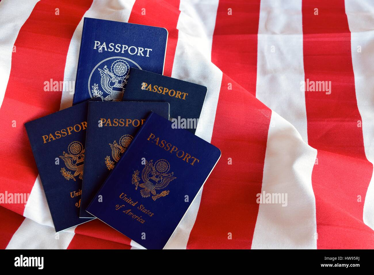 Stripes and Passports / United States citizen passports on the stripes of an american flag. - Stock Image