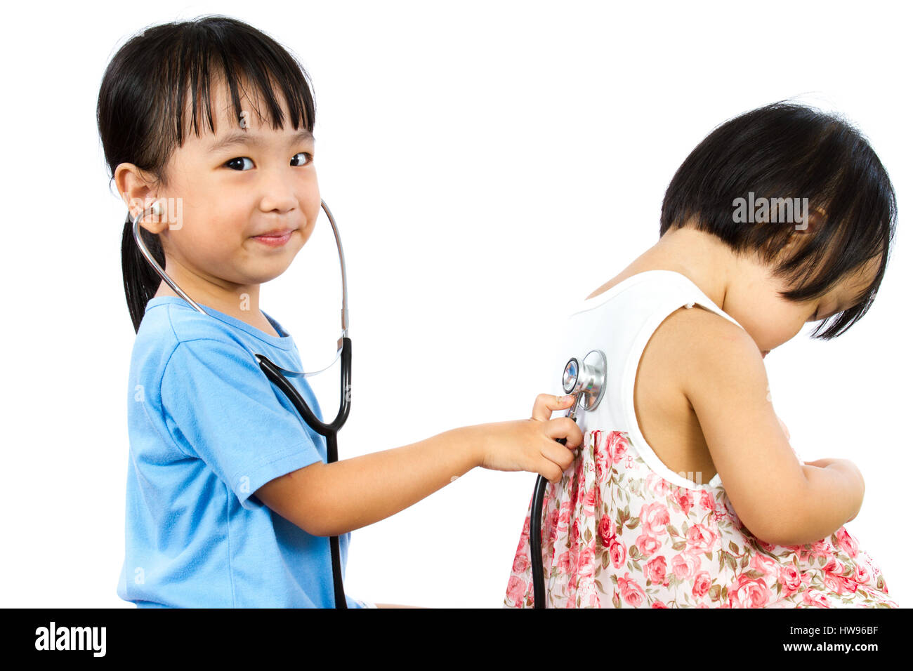 Asian Little Chinese Girls Playing as Doctor and Patient with Stethoscope isolated on white background - Stock Image