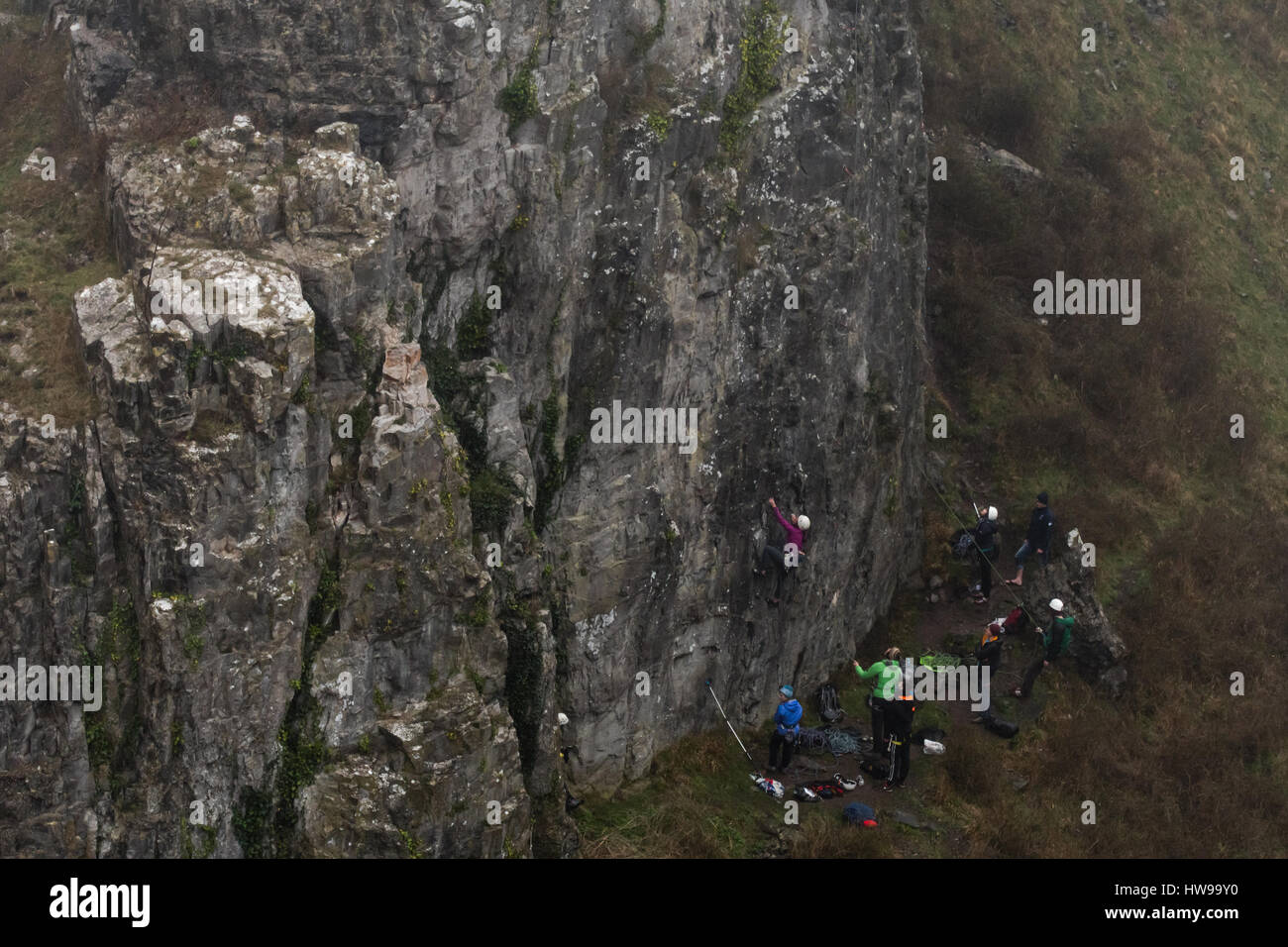 Group of rock climbers in fog at Cheddar Gorge ascend cliff in Somerset, UK, in one of Britain's most impressive Stock Photo