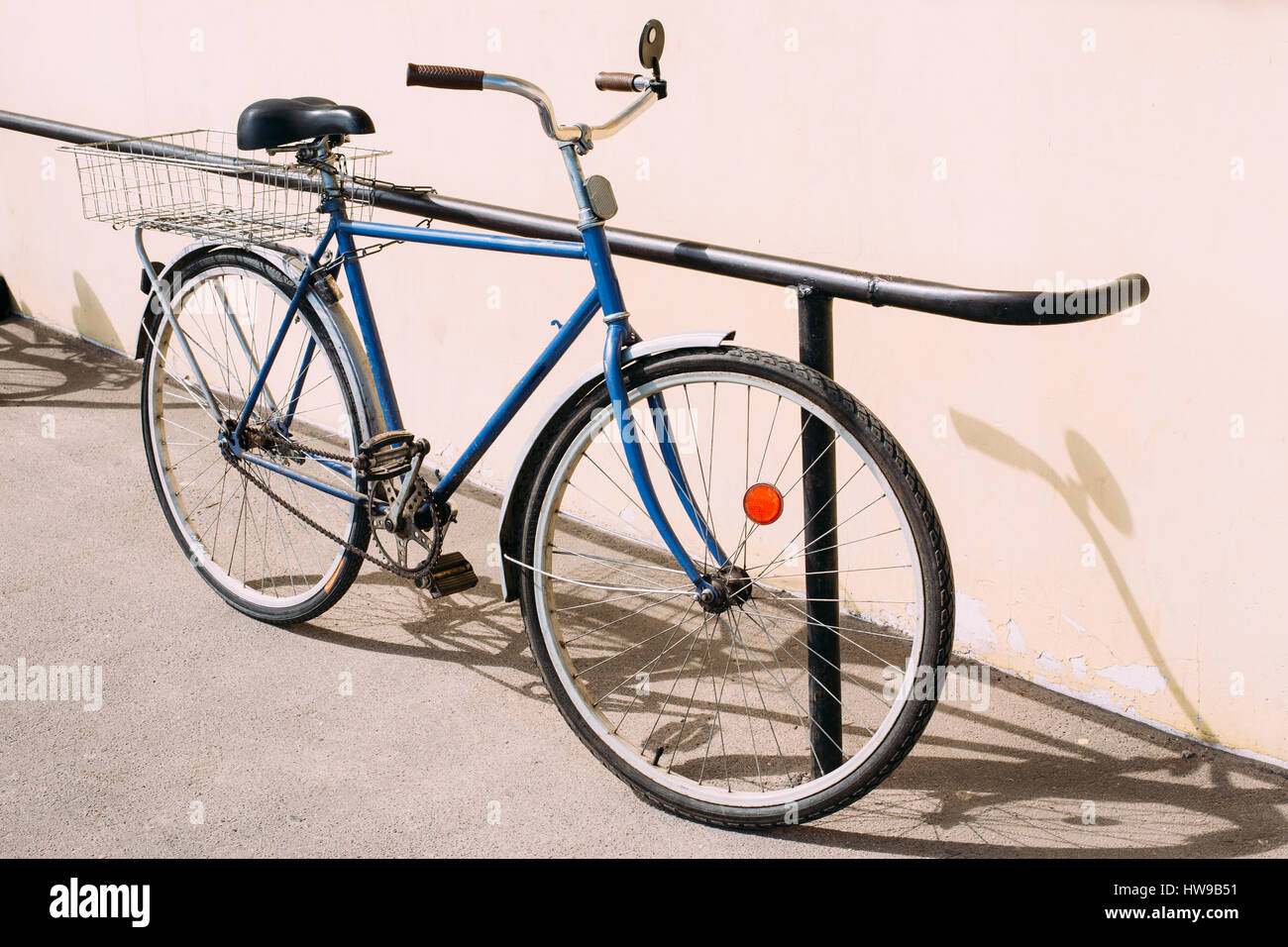 Old Rarity Blue Bicycle Parked Next To Yellow Wall. - Stock Image