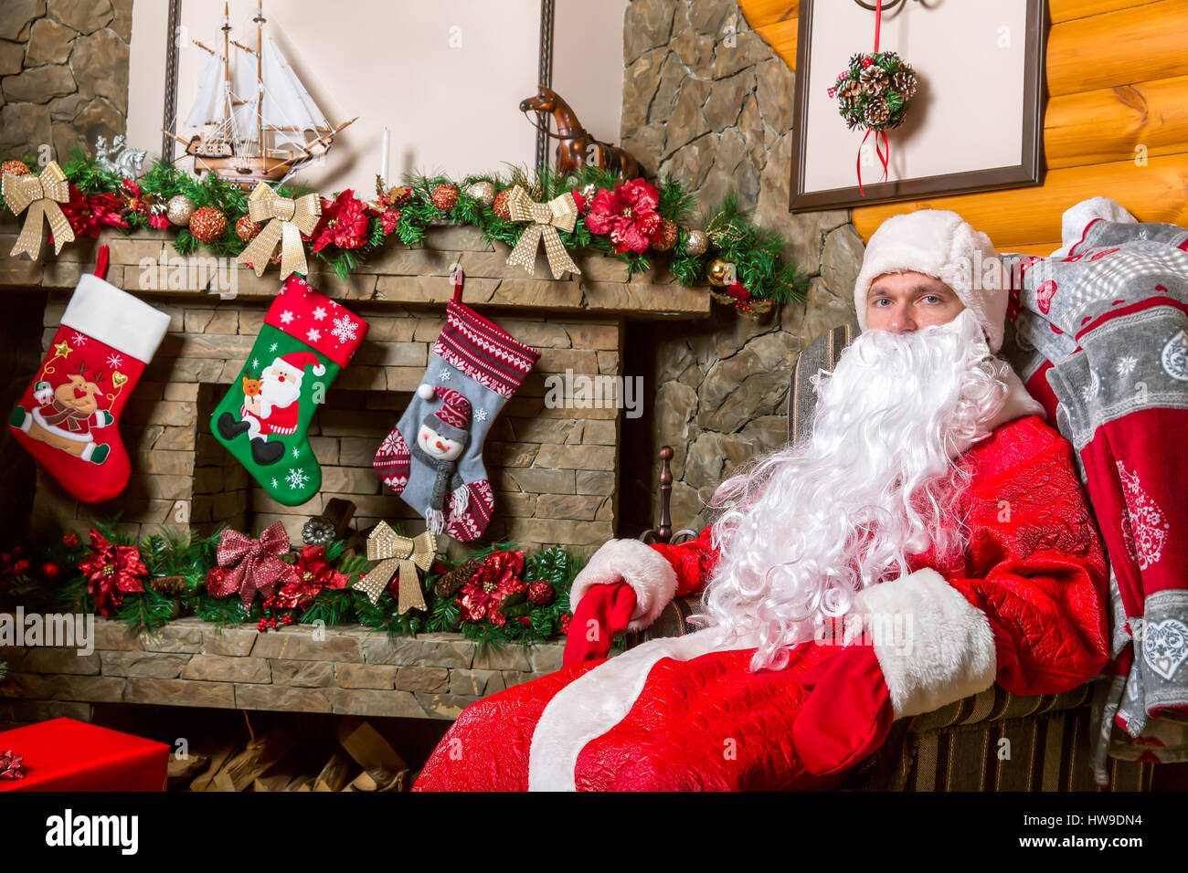 bearded santa claus sitting in a chair gift boxes fireplace and decorated christmas tree on background
