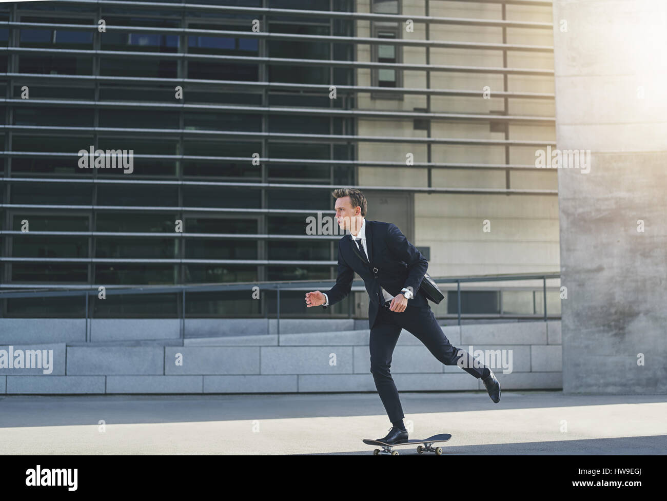 Businessman in a suit on a skateboard pushing himself around - Stock Image