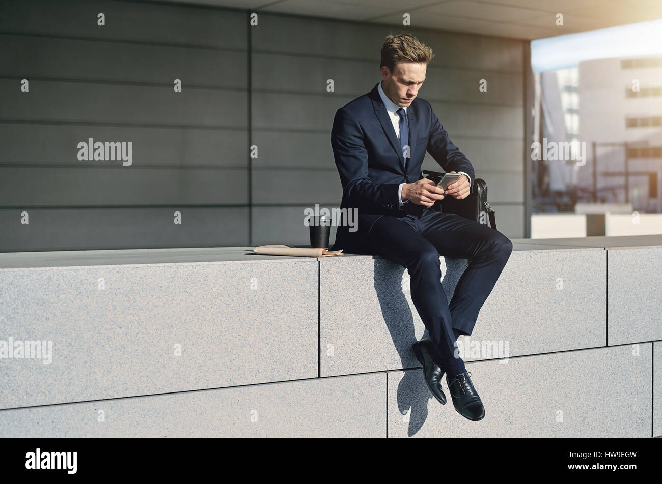 Self-confident businessman with arms crossed searching in smartphone - Stock Image