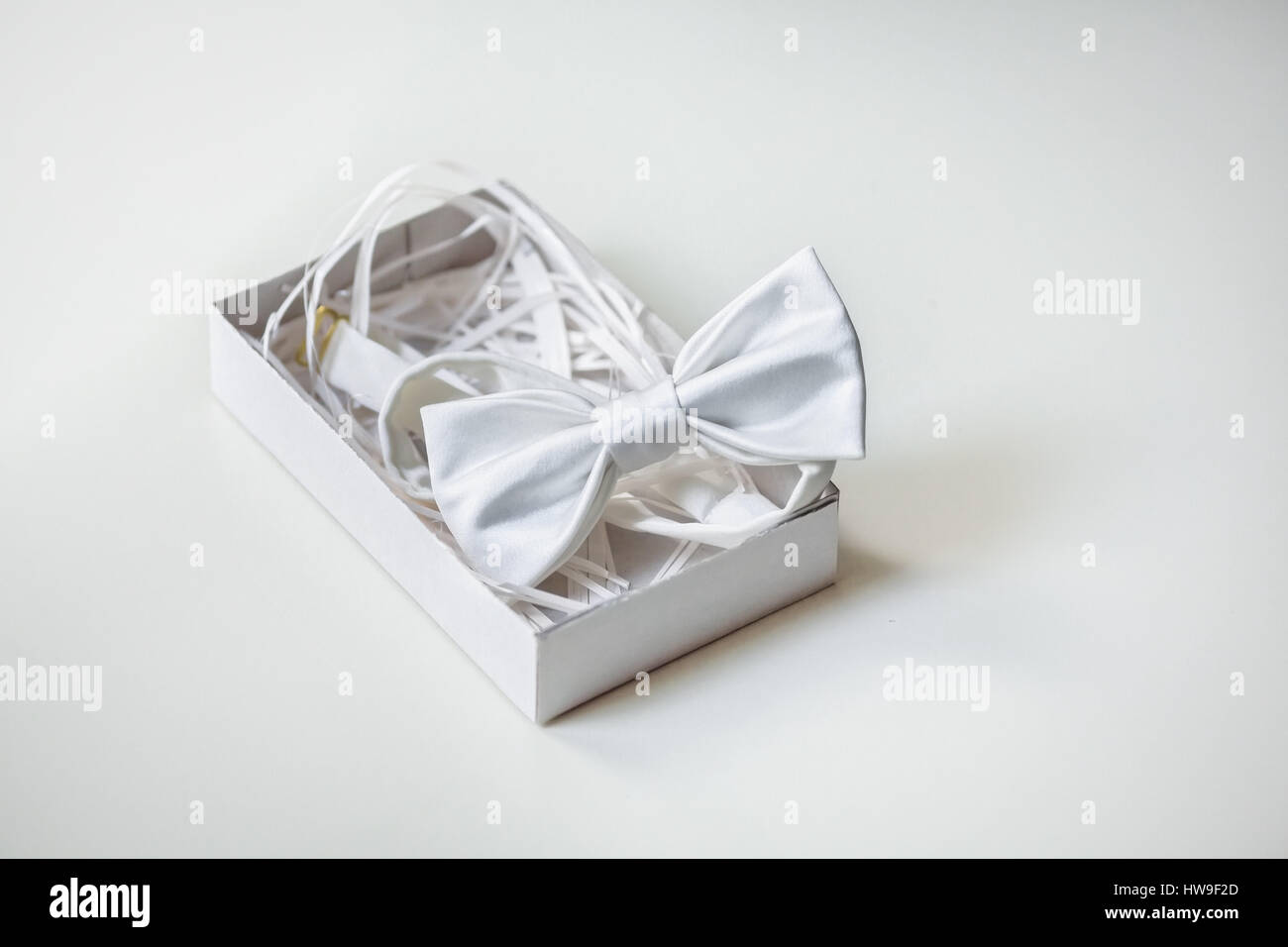 Luxury silk bow-tie in decorated box on light background - Stock Image