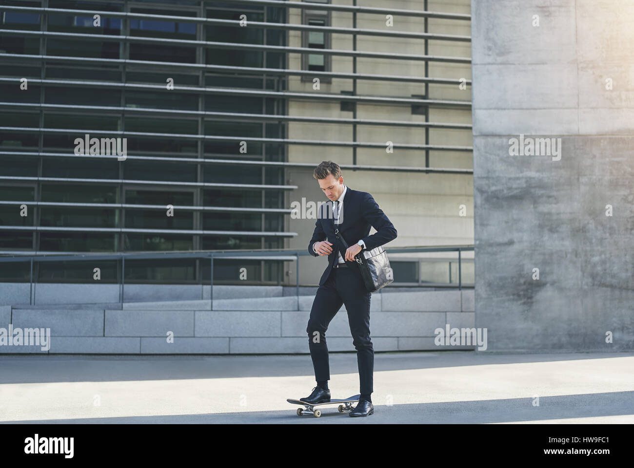 Front view of a businessman adjusting his bag while standing on skateboard - Stock Image