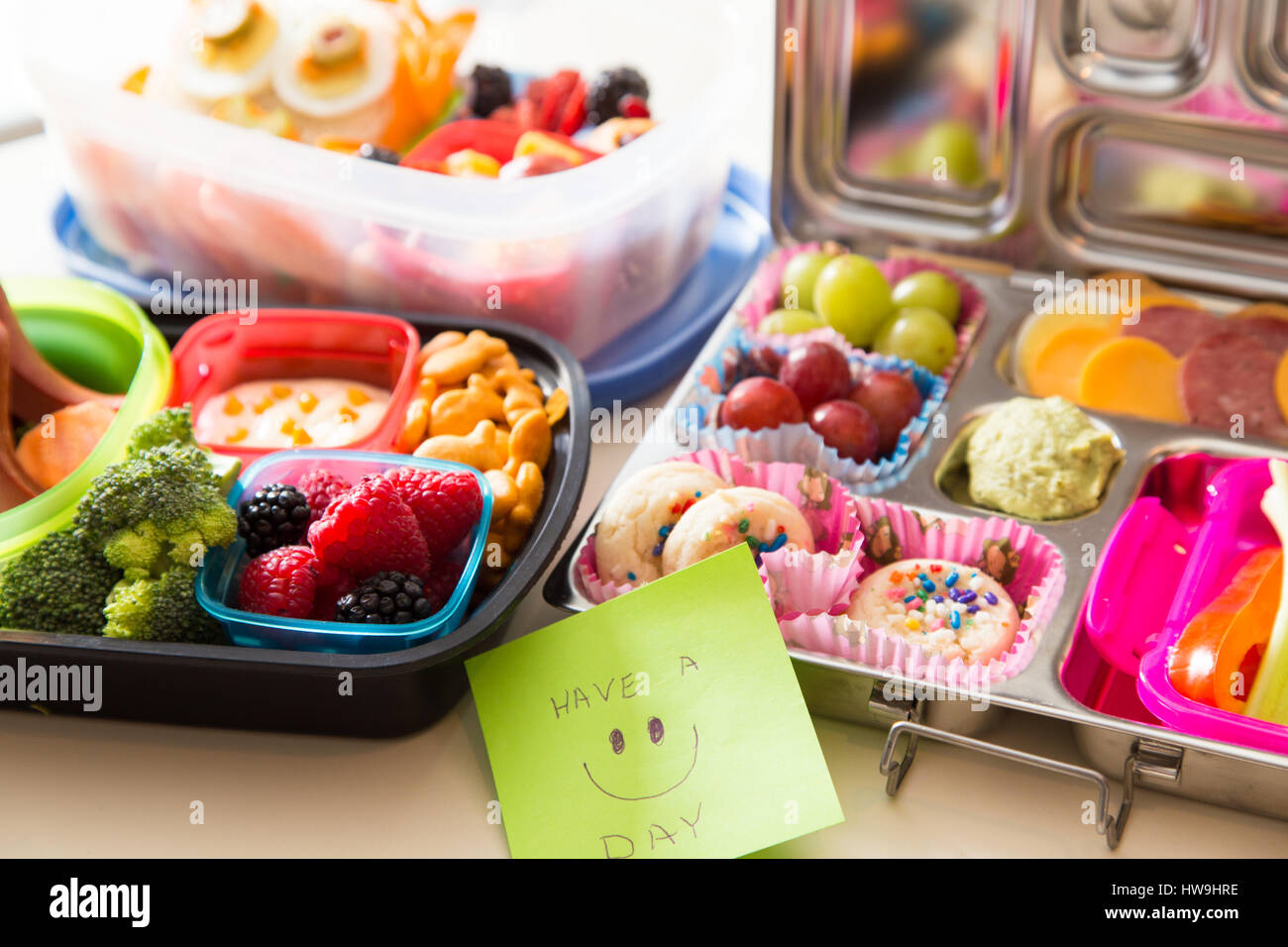 Mom packs a happy note of encouragement with a colorful Bento box lunch packed with healthy fruits, veggies and - Stock Image