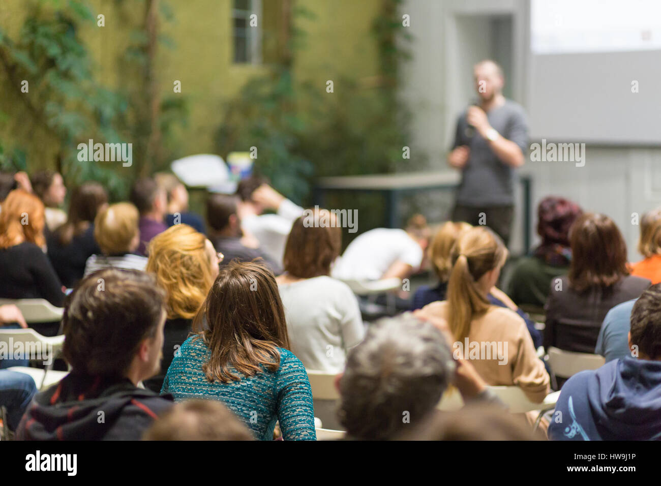 Man giving presentation in lecture hall at university. - Stock Image