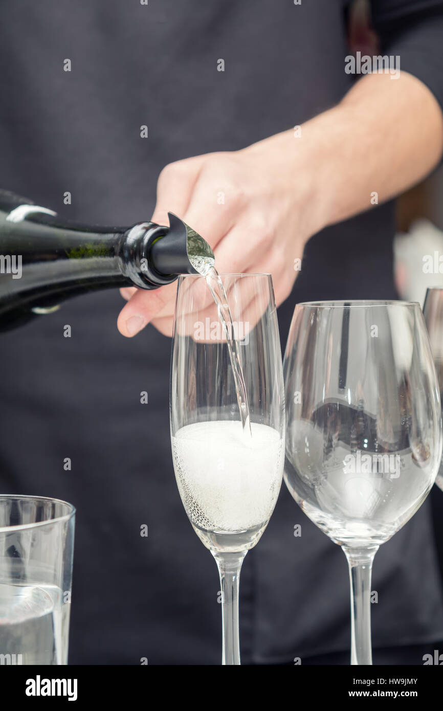 Sommelier pouring sparkling wine to the wine glass. Serving table prepared for event party or wedding. Soft focus, - Stock Image