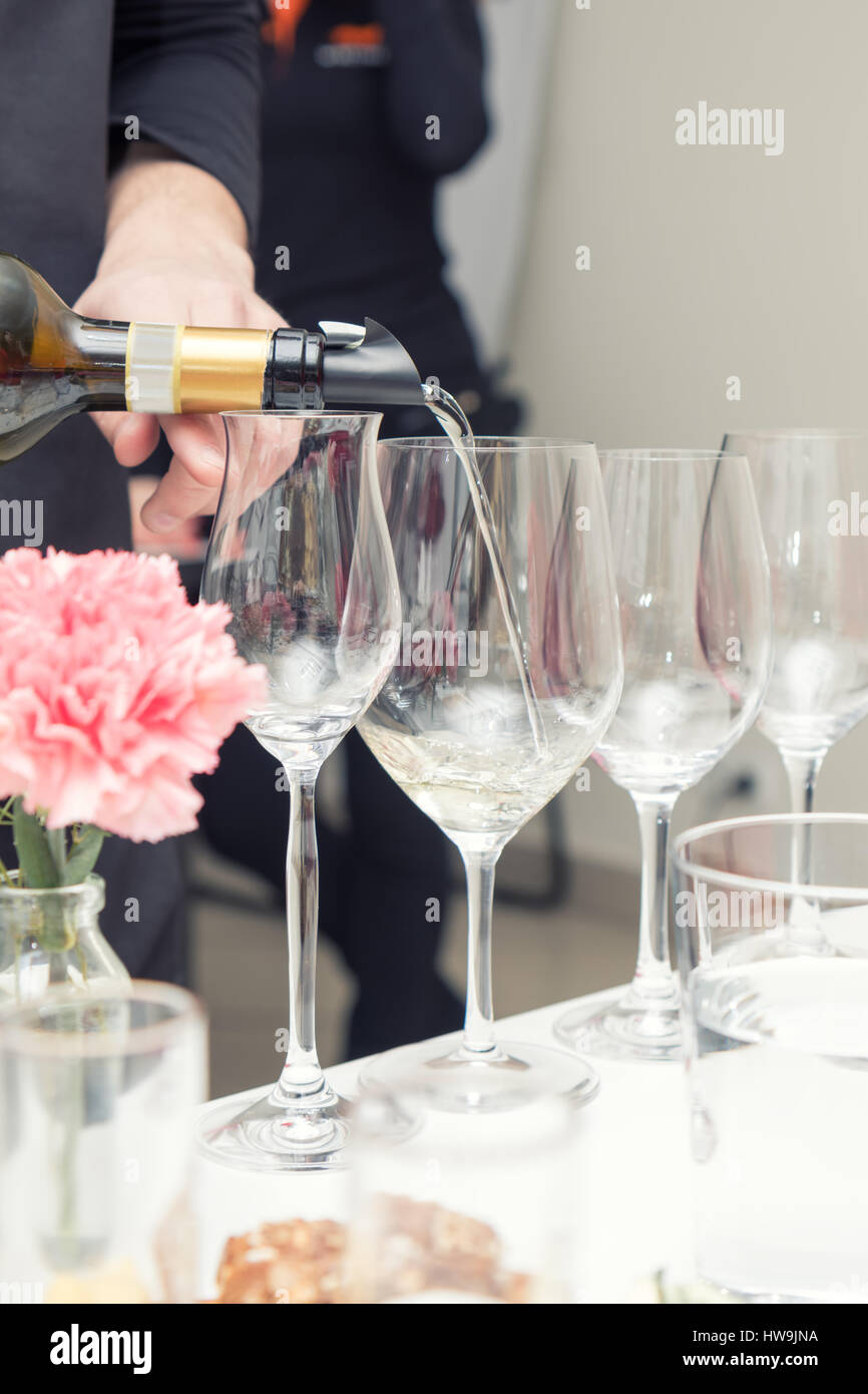 Sommelier pouring white wine to the wine glass. Serving table prepared for event party or wedding. Soft focus, selective - Stock Image