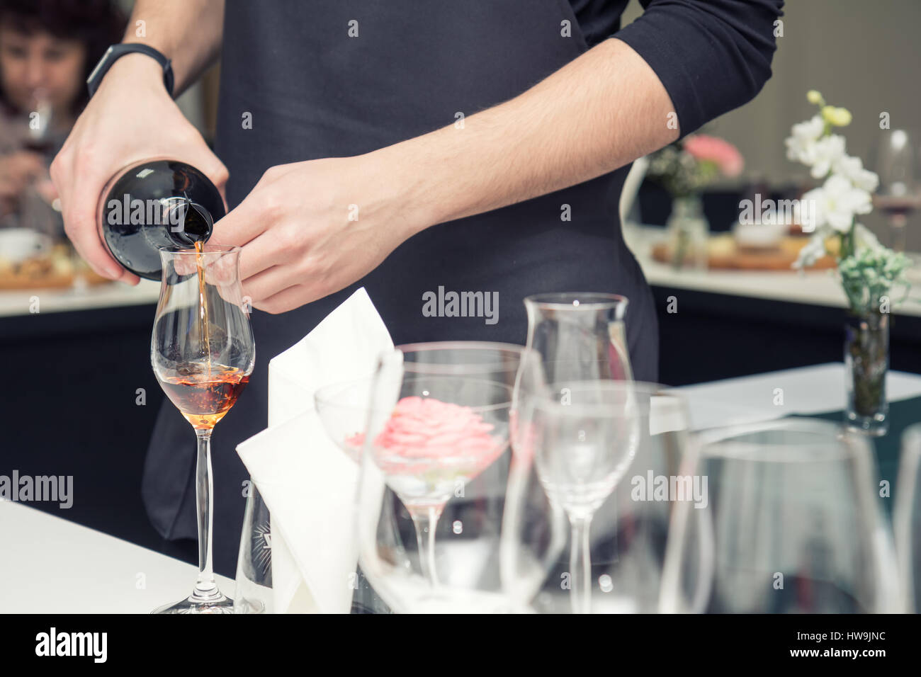 Sommelier pouring rose wine to the wine glass. Serving table prepared for event party or wedding. Soft focus, selective - Stock Image