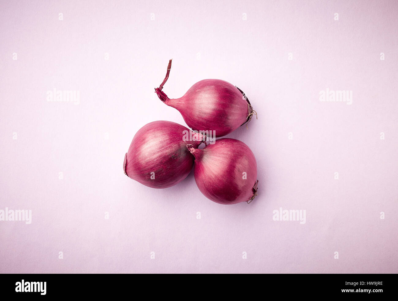 three red onions on purple background, top view - Stock Image