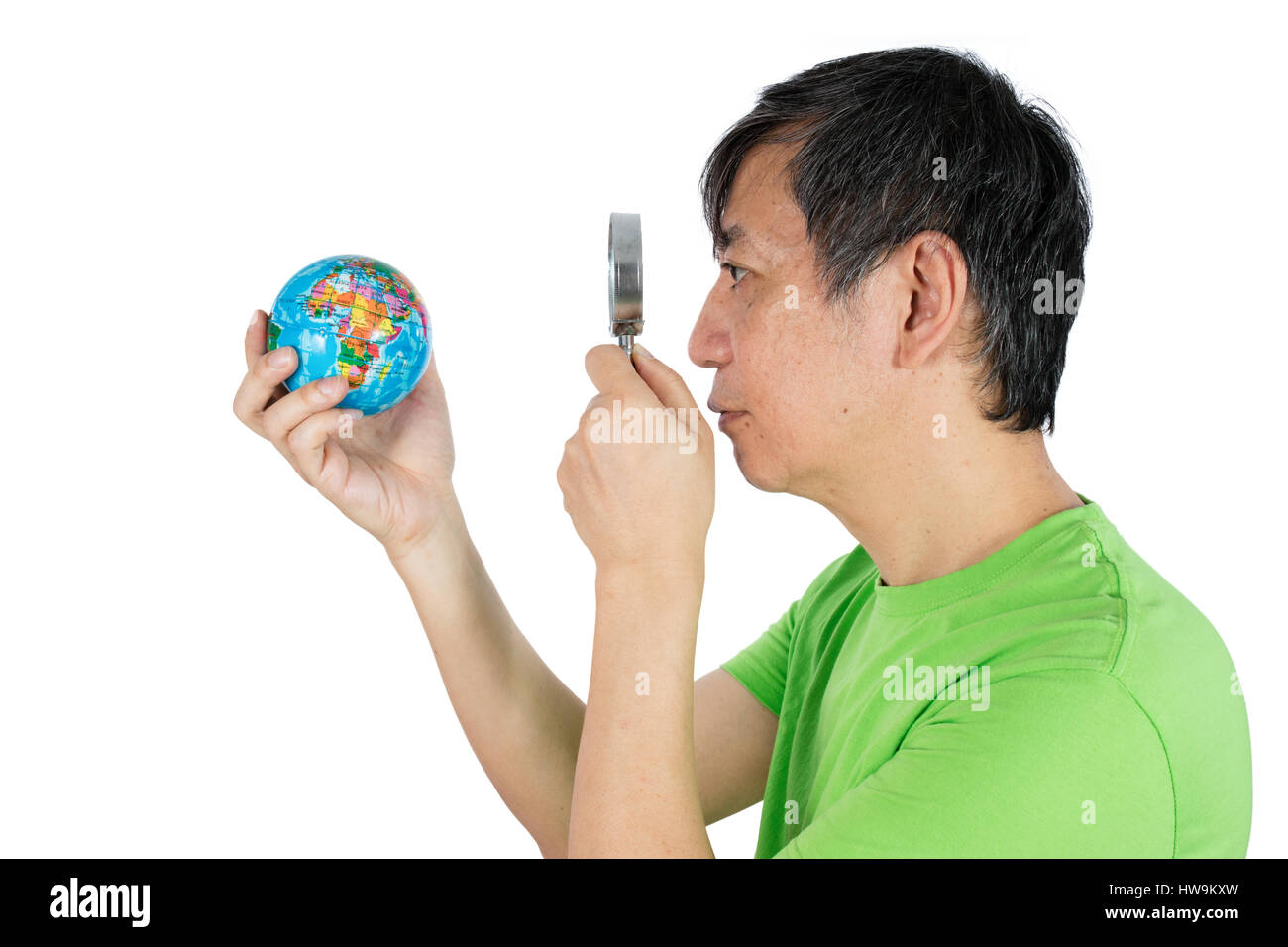 Asian Chinese Man Looking At Globe Through Magnifying Glass in isolated White Background - Stock Image