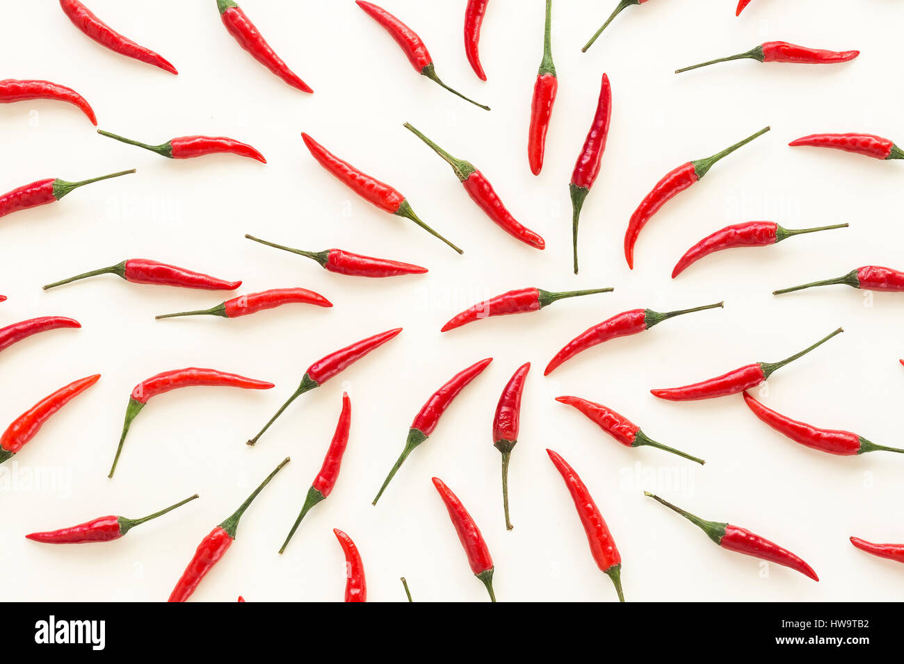 A lot of red hot chili peppers on a white background. a concept hot spice for food. flat lay. Concept red food, - Stock Image