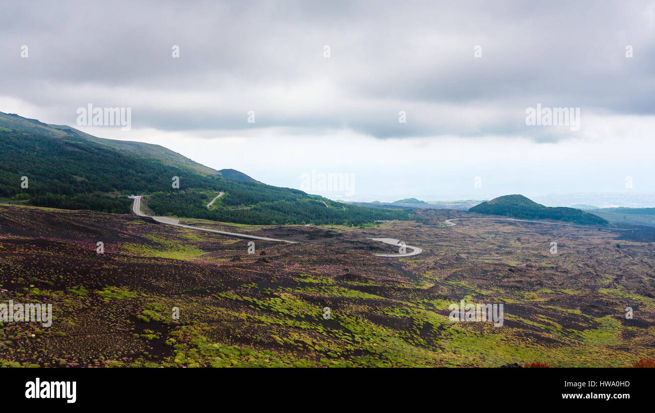 travel to Italy - low cloudy sky over road in lava fields on Mount Etna in Sicily in summer day - Stock Image