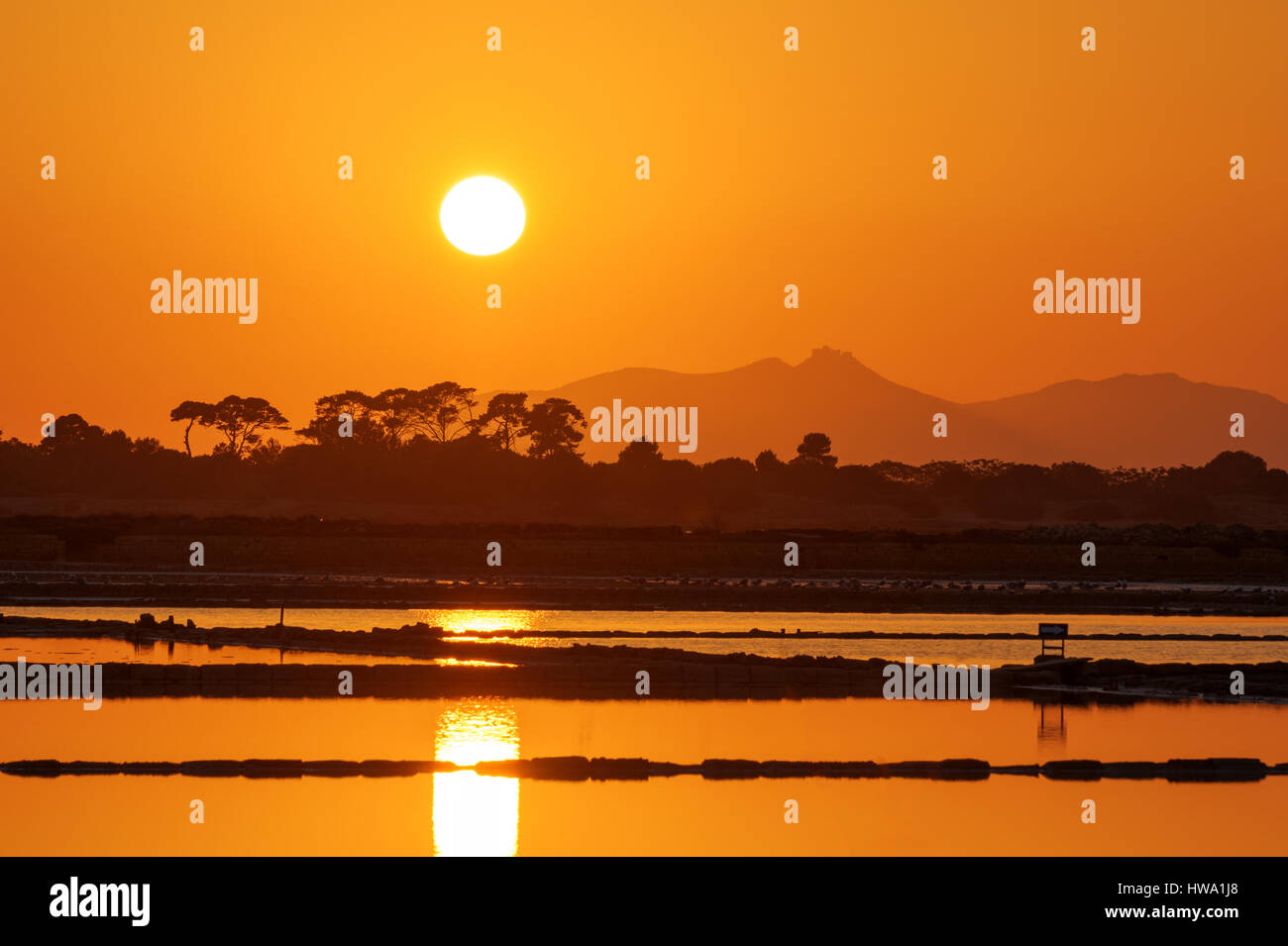 Sunset at the saltpans of Trapani in Sicily Stock Photo